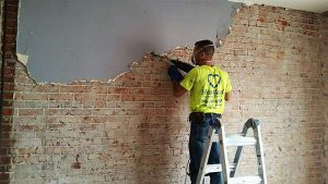 Removing plaster from brick in old downtown building
